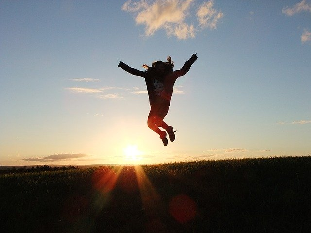 A man jumping in the air with a sunset in the background